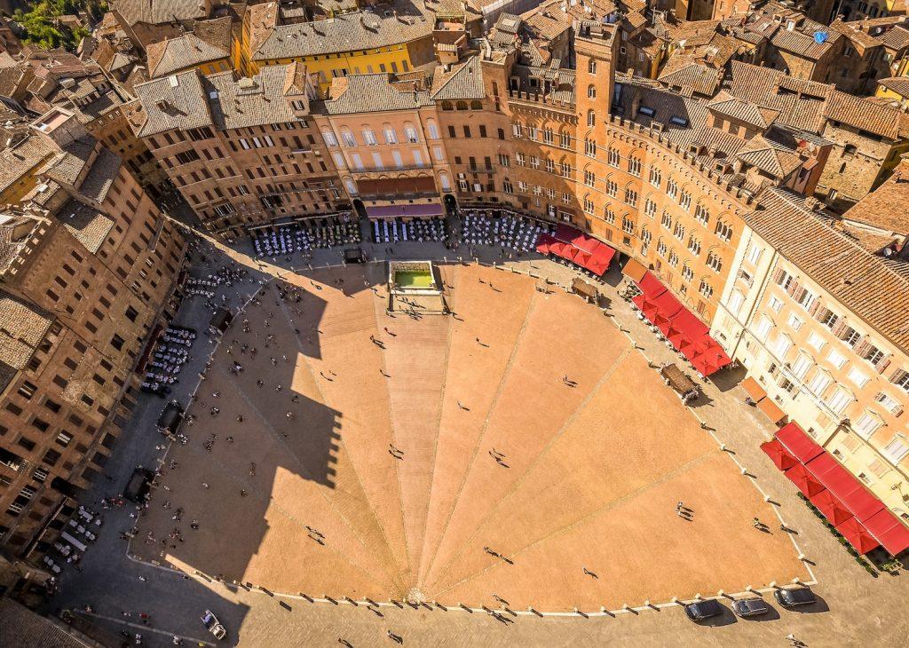 l'immagine ritrae una veduta aerea della famosa Piazza del Campo di Siena, evidenziando il caratteristico color terra di Siena degli edifici.