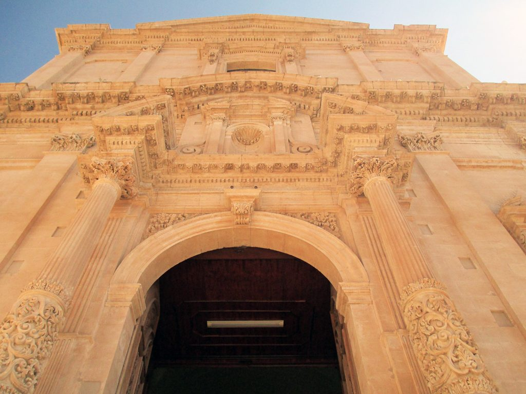 """l'immagine ritrae la facciata di una delle chiese più belle della città di Noto e mette in evidenza la ricchezza dei decori tipici dello stile barocco siciliano ed il colore giallo dorato della pietra locale denominata """"pietra di Noto"""",  utilizzata per la ricostruzione di tutta la città."""
