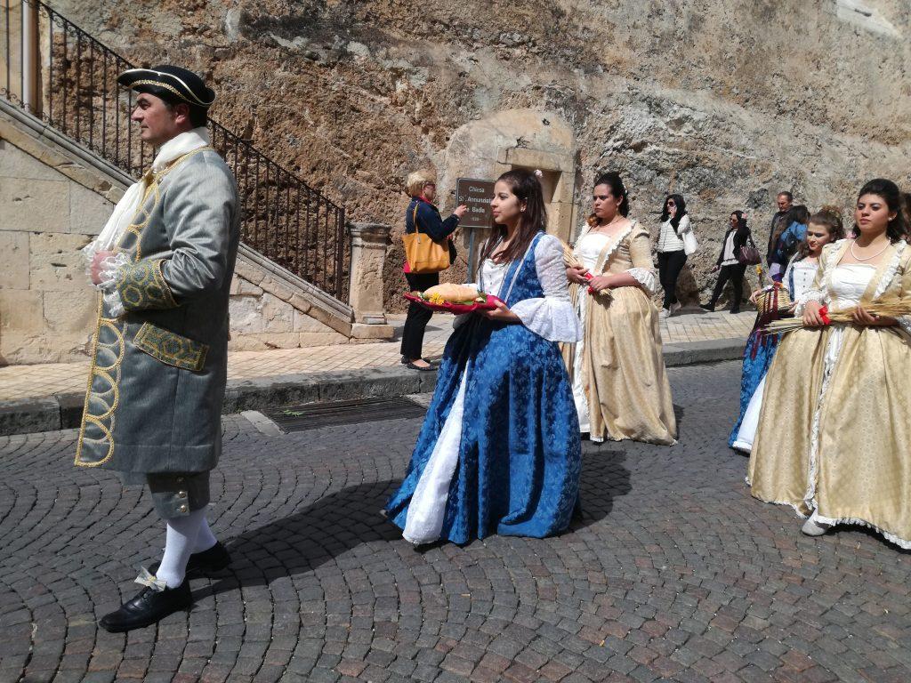 l'immagine ritrae la sfilata del corteo barocco organizzato in occasione dell'infiorata di Noto, la  capitale del barocco siciliano. In primo piano alcuni figuranti mentre sfilano per le vie del borgo in tipici abiti del 1700.