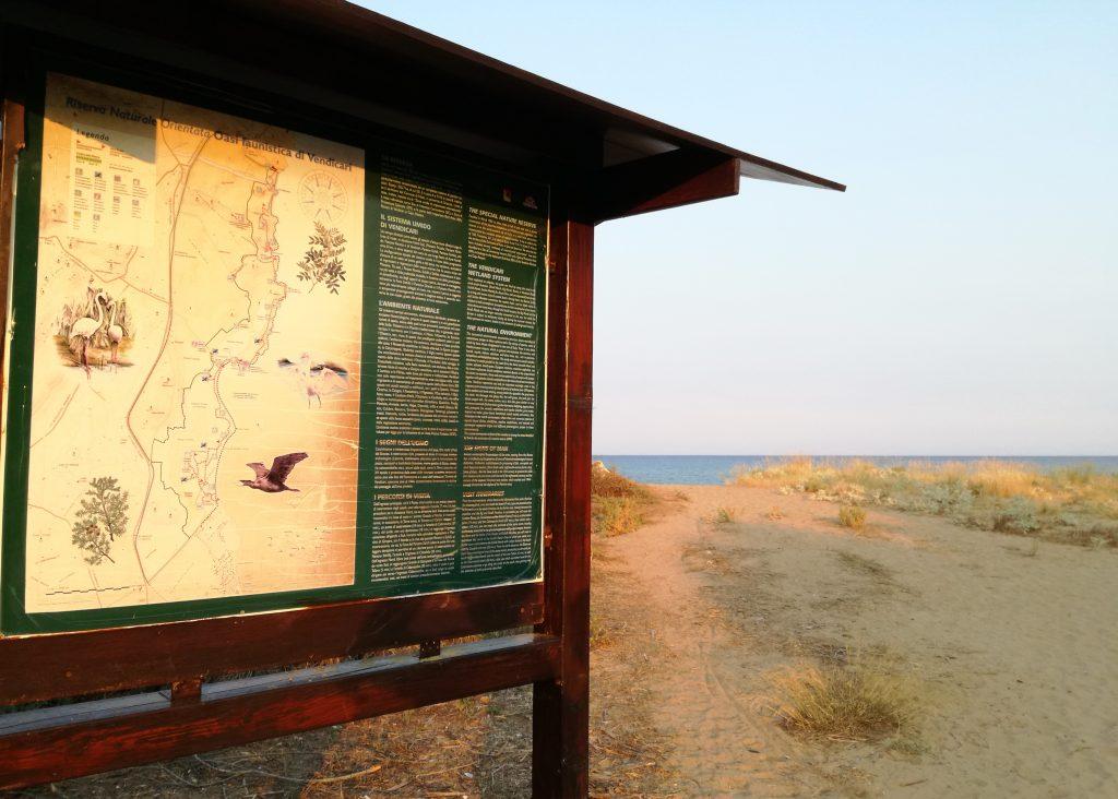 L'immagine in primissimo piano ritrae un pannello illustrativo riguardante la riserva naturale orientata oasi faunistica di Vendicari, appartenente al territorio di Noto, la capitale del barocco siciliano. Sullo sfondo ci sono delle dune di sabbia, della macchia mediterranea e si intravede il mare e la linea dell'orizzonte. La foto è scattata al tramonto, quindi prevalgono i toni caldi.
