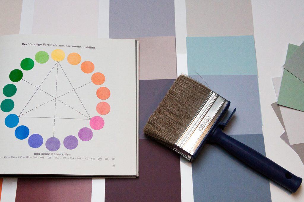 l'immagine rappresenta un cerchio cromatico e un pennello largo da parete, entrambi poggiati su cartoncini colorati