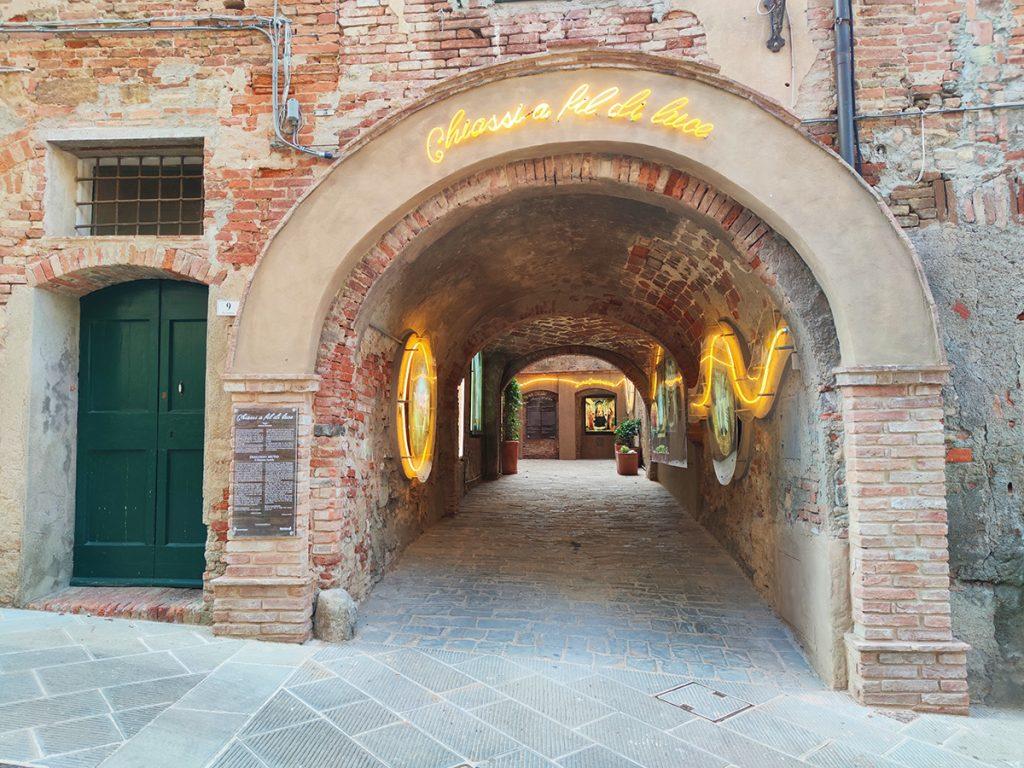 l'immagine mostra l'iniziativa Chiassi a fil di luce del borgo medievale di Peccioli, ovvero uno dei vicoli (i chiassi appunto) decorati ed illuminati da artisti locali.