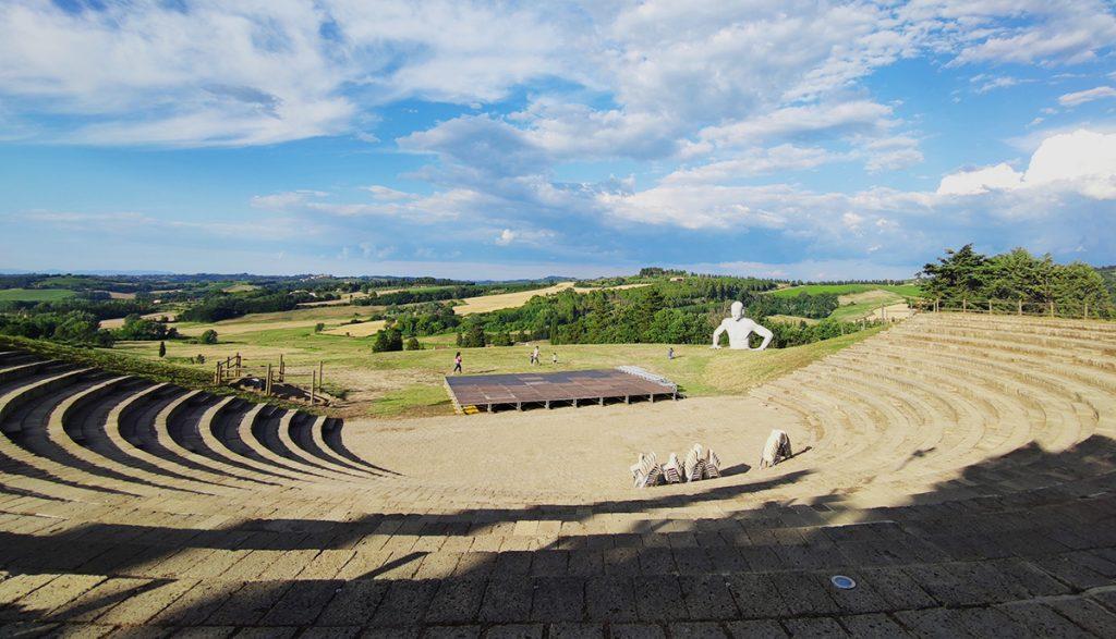 """l'immagine ritrae l'anfiteatro di Fonte Mazzola nel borgo medievale di Peccioli, con le campagne toscane sullo sfondo e sulla destra una delle 4 statue dell'installazione """"presenze"""", collocate per tutto il territorio."""