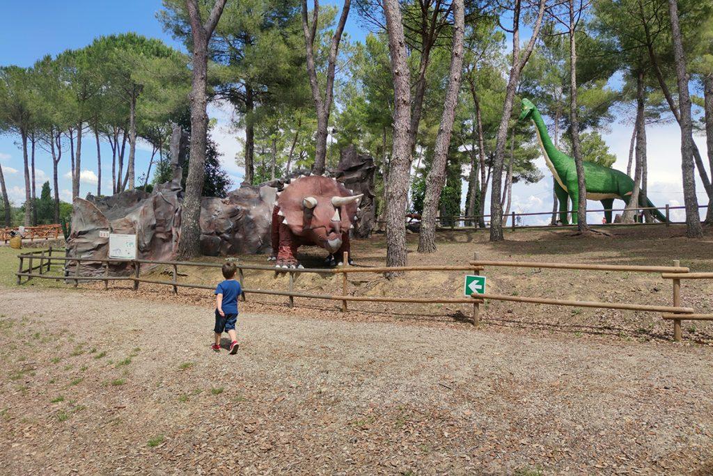 l'immagine rappresenta una zona del parco preistorico di Peccioli, in cui si vede mio figlio che cammina verso un triceratopo rosso, mentre sullo sfondo si vede la pineta e l'altissimo Brachiosauro verde