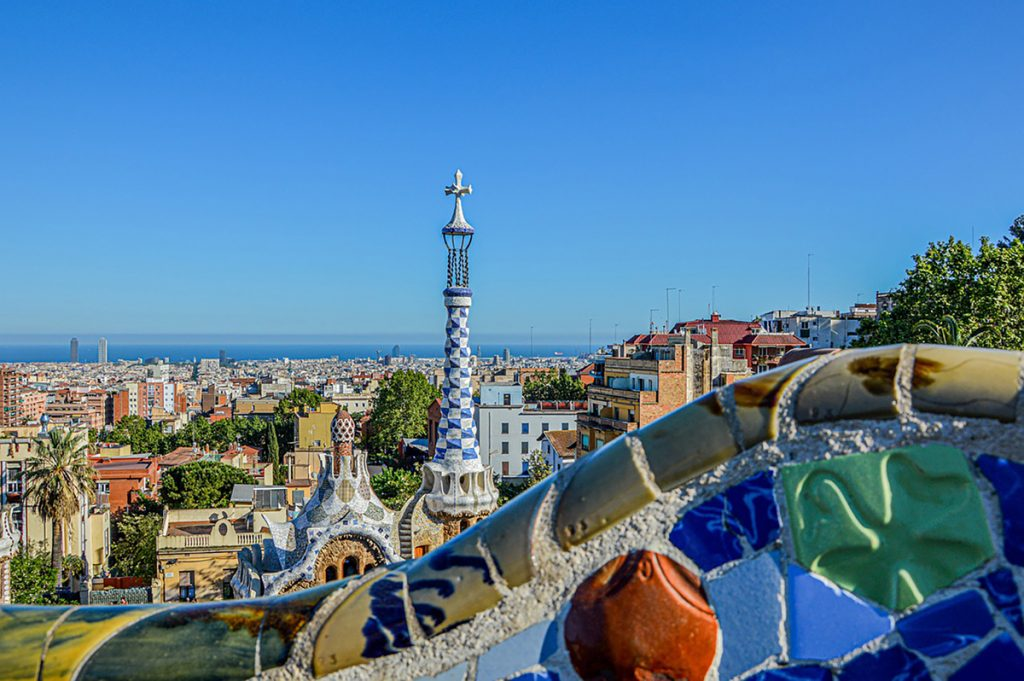 l'immagine rappresenta in primo piano i fantastici colori dei  mosaici di Parc Guell e di Casa del Guarda, detti trecadìs e tipici di Barcellona, mentre sullo sfondo si intravede il resto della città e del suo mare