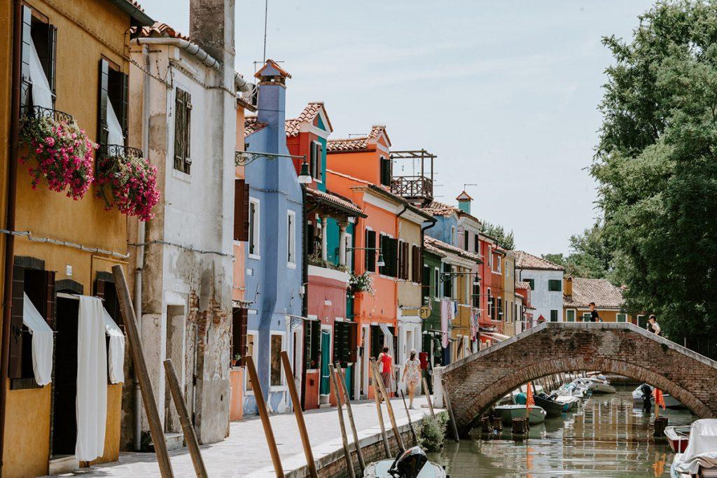 l'immagine ritrae uno scorcio dell'isola di Burano, mostrando le tipiche case multicolori e uno dei canali con i suoi ponti